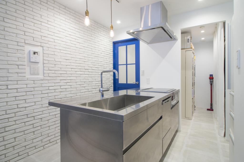 ブルーのドアとステンレスキッチンで印象的な空間に