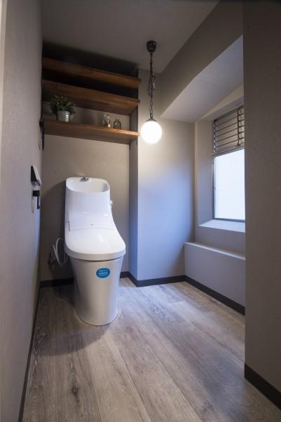 木質系の素材の棚が設置されたシンプルなトイレ