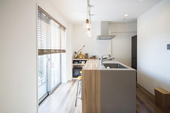 壁付けのL字型キッチンは、明るいバルコニーを向く対面タイプに変更